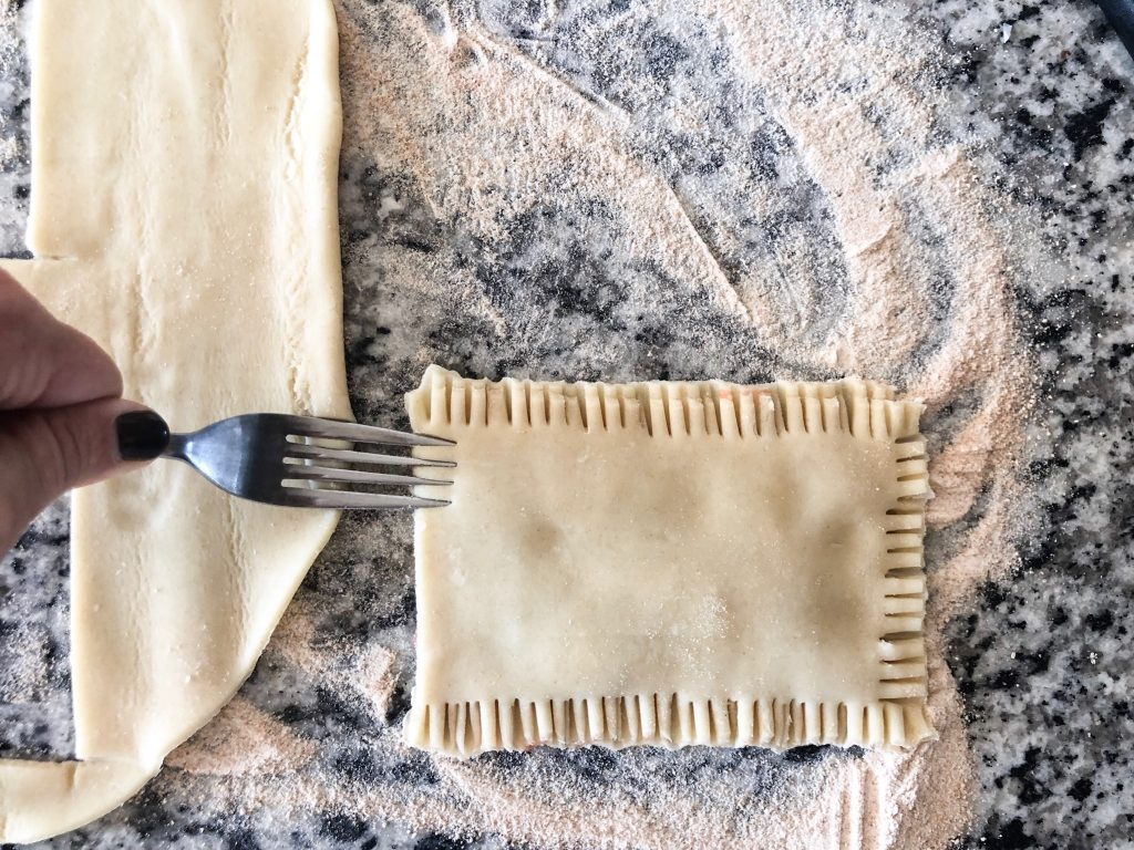 Picture of fork molding rectangle pie crust together to make homemade air fryer pop tart.