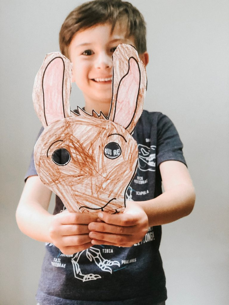 Boy holding up Llama Llama paper plate craft